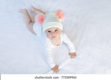Cute adorable baby child with warm white and pink hat with cute bobbles. Happy baby girl learning crawl and looking at the camera. Close-up for xmas holiday and family concept.