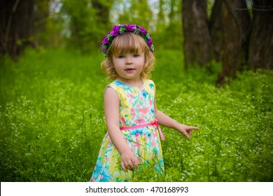cute adorable baby girl in nice flower dress staying in the field with green grass