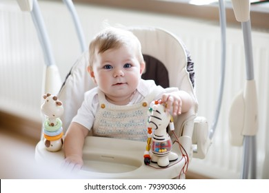 Cute adorable baby sitting in swing, indoors. Closeup of peaceful child, little baby girl swinging and playing. Looking on toys. Family, birth, new life. Attentive child.