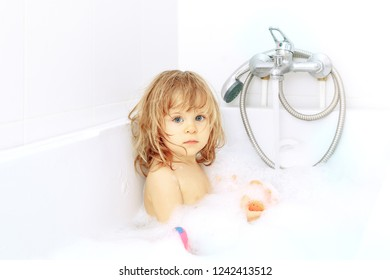 Cute adorable baby taking bath in washing sink on water tap background. Little healthy girl with big blue eyes having fun and playing with soap foam. Looking up seriously. Toy in hands.