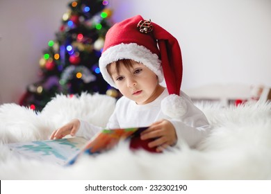 Cute adorable boy reading a book in front of the christmas tree, christmas time