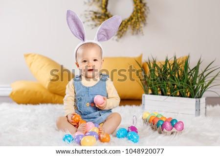 240807efe53 Cute adorable Caucasian baby girl in jeans dress wearing purple bunny ears  sitting in studio.