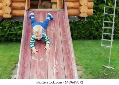Cute adorable caucasian toddler boy having fun sliding down wooden slide at eco-friendly natural playground at backyard in autumn. Playful funny child portrait enjoying outdoor sport acitivities.