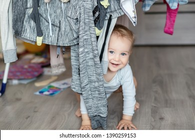 Cute adorable caucasian toodler boy laughing and having fun playing home with mess and clothes dryer on background. portrait of Funny playful baby at nursery room. Happy and carefree childhood concept