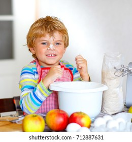 Cute adorable funny blond kid boy baking apple cake in domestic kitchen. Child having fun with working with mixer, flour, eggs and fruits. With flour on nose