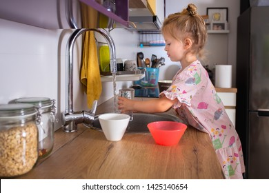 The cute and adorable girl fills a glass with water from a water tap in the kitchen.