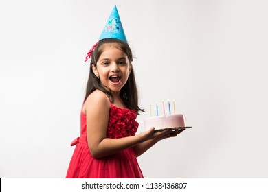 Cute adorable little Indian/asian small girl celebrating birthday while holding strawberry cake and blowing candles at table or standing isolated over white or red background