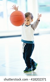 Cute adorable little small white Caucasian child toddler boy playing with ball in gym, having fun, healthy lifestyle childhood concept