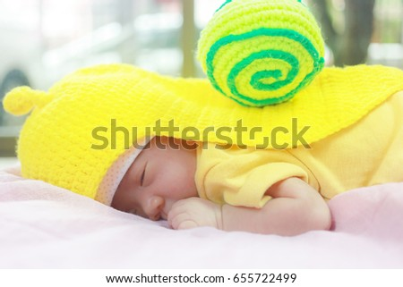 52332ebd2b68 Cute adorable newborn baby 20 day sleeping in pink bed colorful of clothes.  Newborn child