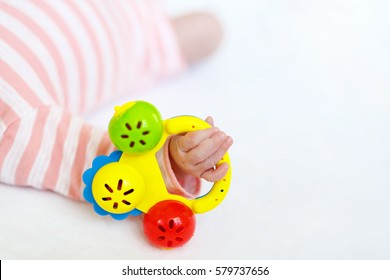 Cute adorable newborn baby playing with lots of colorful rattle toys on white background. Closeup of New born child, little girl and hand holding toy. Family, new life, childhood, beginning concept