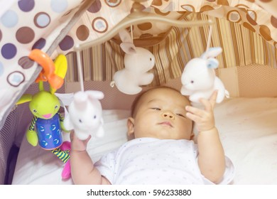 Cute adorable newborn baby playing on colorful toy gym