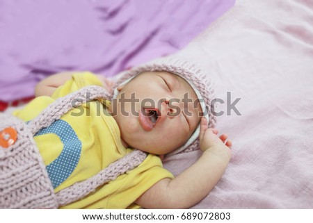 745fc9ea5724 Cute adorable newborn baby twenty day sleeping in pink bed colorful of  clothes. Newborn child