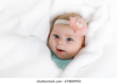 Cute adorable newborn baby in white bed and wrapped in blanket. New born child, little girl looking surprised at the camera. Family, new life, childhood, beginning concept.