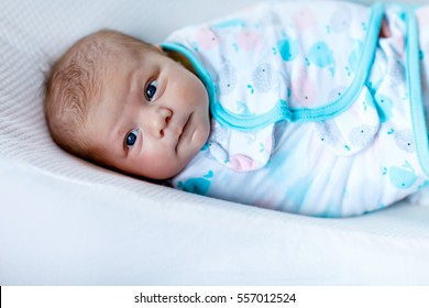 Cute adorable newborn baby wrapped in colorful blanket, looking at the camera. Closeup of peaceful child, little baby girl after sleeping. Family, Birth, new life. Swaddling as method for calm child