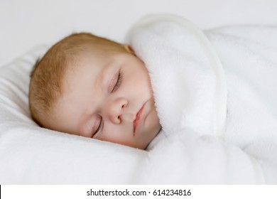 Cute adorable newborn baby wrapped in white blanket, sleeping in kids bed or cocoon. Closeup of peaceful child, little baby girl sleeping. Swaddling as method for calm down child