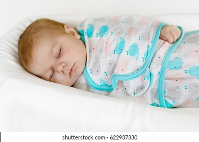 Cute adorable newborn baby wrapped in colorful blanket, sleeping in kids bed or cocoon. Closeup of peaceful child, little baby girl sleeping. Swaddling as method for calm child