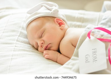 Cute adorable newborn baby wrapped in white blanket, sleeping in bed
