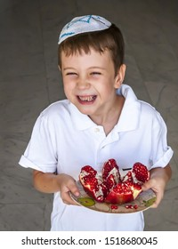 Cute adorable positive laughing Jewish Caucaisian boy with a kippah on his head holding a plate of split pomegranate fruit. Rosh Hashaha concept image.