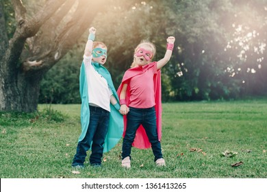 Cute adorable preschool Caucasian children boy and girl playing superheroes. Two kids friends having fun together outdoors in park. Happy active childhood and friendship concept.