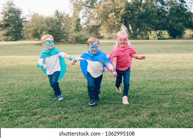 Cute adorable preschool Caucasian children playing superheroes. Three kids friends having fun together and running outdoors in park. Happy active childhood and friendship concept.