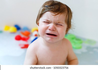 Cute adorable sad baby girl taking foamy bath in bathtub. Crying toddler playing with bath rubber toys. Beautiful child do not washing hairs