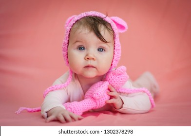 Cute and adorable six months old baby child lying on her belly and looking in the camera with a pink teddy bear and pink background.