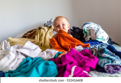 Cute, Adorable, Smiling, Caucasian Baby Sitting in a Pile of Dirty Laundry on Bed