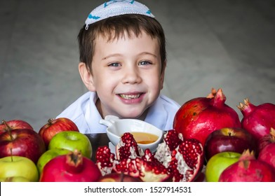 Cute adorable smiling Jewish Caucasian boy with a kippah on his head sitting by a plate of split pomegranate and other fruit, looking at the camera. Rosh Hashaha concept image.