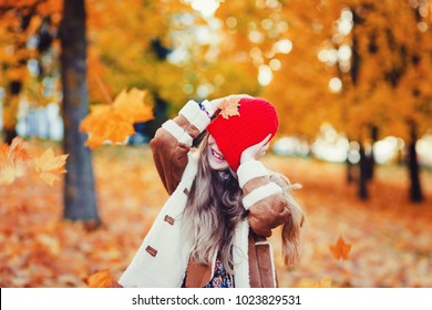 Cute adorable smiling little caucasian girl child standing in autumn fall park outside. Happy lifestyle childhood concept