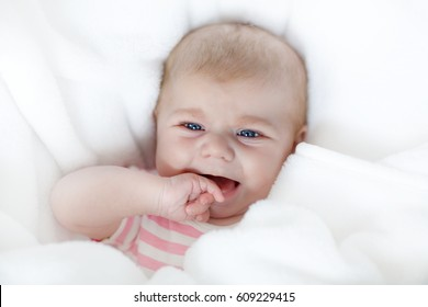 Cute adorable two months baby sucking fist as getting first tooh. Closeup of peaceful child, little baby girl. Looking the camera. Wrapped in white blanket. Family, birth, new life. Attentive child.