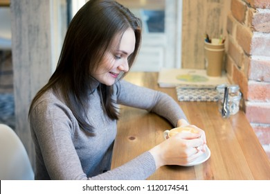 Cute adult young woman sitting near window in casual clothes (sweater and jeans), looking sideways thoughtful. Copy space