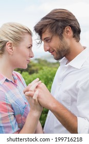 Cute affectionate couple standing outside holding hands on a windy day