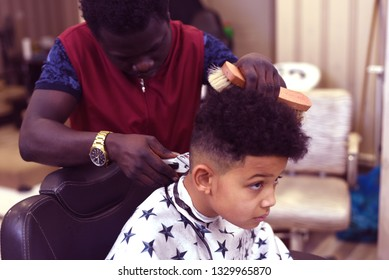 Cute african american boy in the african barbershop. Cute mixed boy makes a haircut in the African salon. Hair style. Haircut by machine for children. School boy hair style. Haircut by scissors.