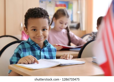 Cute African American boy doing homework in classroom at school