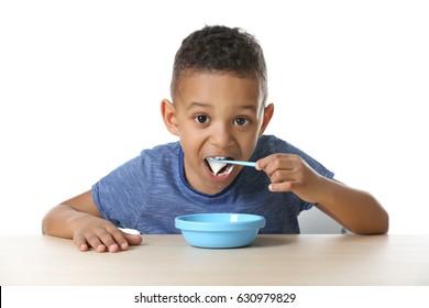 Cute African American boy eating yogurt on white background