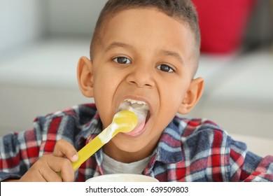 Cute African American boy eating yogurt at home, closeup
