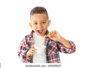 Cute African American boy eating yogurt on light background