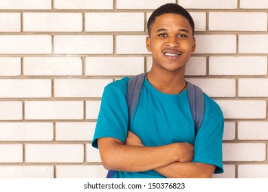 cute african american college boy leaning against a wall with arms crossed