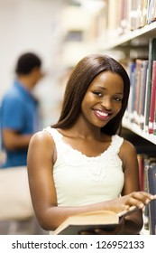 cute african american college girl reading in library