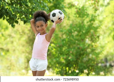 Cute African American girl with ball in park