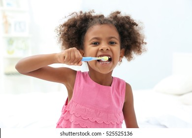 Cute African American girl brushing teeth in bathroom