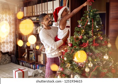 Cute African American girl decorating Christmas tree with smiling father.
