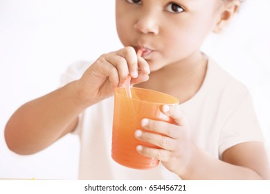 Cute African American girl drinking juice at home, closeup