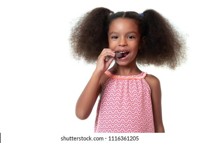 Cute african american girl eating a chocolate cookie - Isolated on white