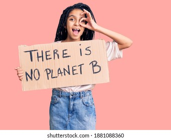 Cute african american girl holding there is no planet b banner smiling happy doing ok sign with hand on eye looking through fingers