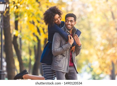 Cute african american girl jumped on boyfriend back, having fun while walking by autumn forest, copy space