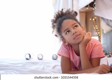 Cute African American girl lying on bed