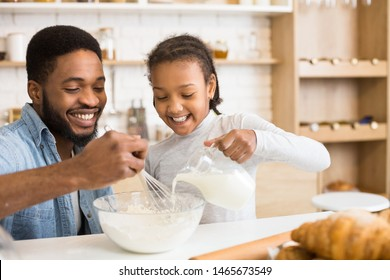 Cute African American Girl Pouring Milk Into Bowl At Kitchen, dad mixing the dough, copy space