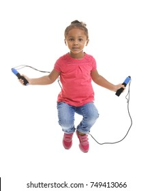 Cute African American girl skipping rope on white background