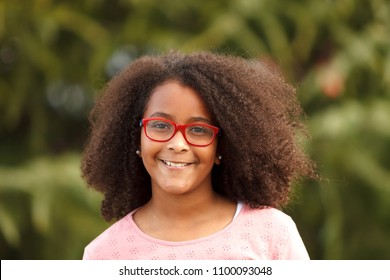 Cute African American girl smiling in the street with afro hair